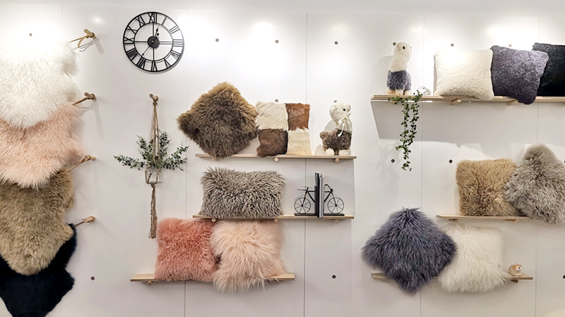 A wall of Glory Wisdom Corp showroom displaying sheepskin rugs and decorative pillows